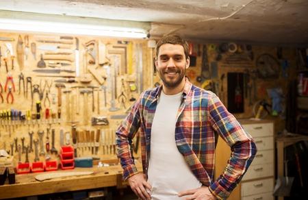 profesión, la gente, la carpintería y la gente concepto - hombre feliz o carpintero en camisa de cuadros coloca en la pared taller con herramientas de trabajo