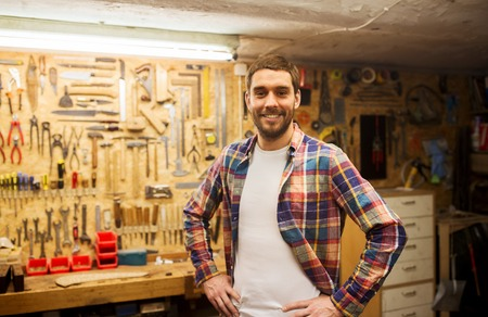 profession, people, carpentry and people concept - happy man or carpenter in checkered shirt standing at workshop wall with work tools