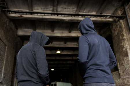 criminal activity, addiction, people and social problem concept - close up of addict men or criminals in hoodies on street Stock Photo