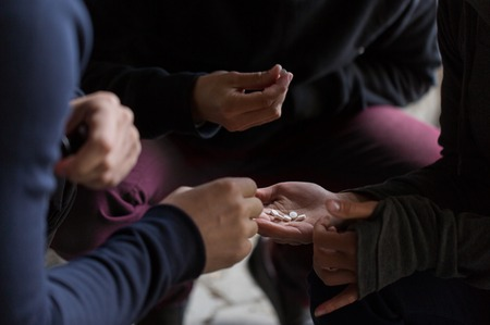 junky: substance abuse, addiction and people concept - close up of addicts using drugs outdoors