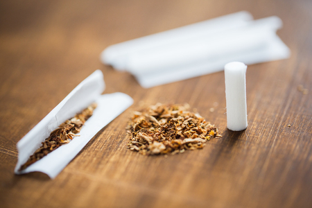 nicotine: drug use, substance abuse, nicotine addiction and smoking concept - close up of marijuana or tobacco with cigarette paper and filter Stock Photo