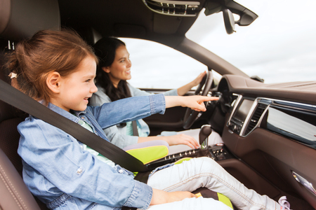 family, transport, road trip and people concept - happy woman with little daughter driving in car Banque d'images