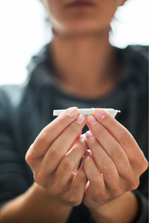 substance abuse: drug use, substance abuse, addiction and people concept - close up of addict hands with marijuana joint Stock Photo