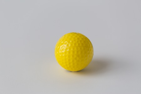 objects equipment: sport, fitness, game, sports equipment and objects concept - close up of yellow golf ball