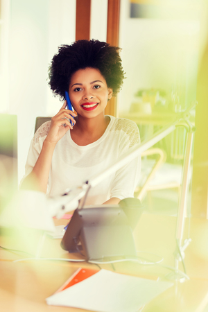 creative concept: business, startup and people concept - happy african american businesswoman or creative worker calling on smartphone at office
