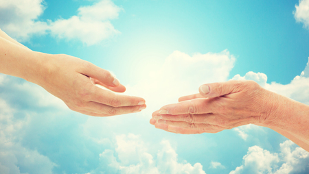 cupped: people, age, family, care and support concept - close up of senior woman and young woman reaching hands out to each other over blue sky and clouds background