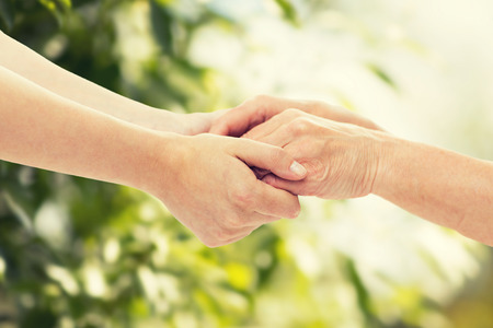 people, age, family, care and support concept - close up of senior woman and young woman holding hands over green natural background
