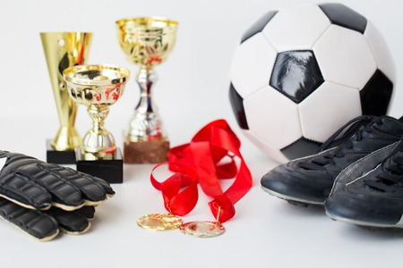 football boots: sport, achievement, championship and success concept - close up of soccer ball, football boots and goalkeeper gloves with golden medals and cups