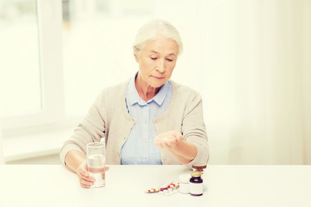 health care and medicine: age, medicine, health care and people concept - senior woman with pills and glass of water at home Stock Photo