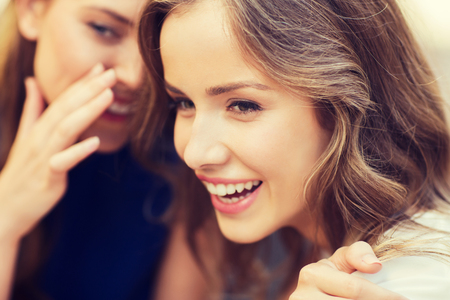 people, communication and friendship concept - smiling young women gossiping and whispering secrets Stock Photo