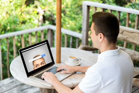 work at home: business, internet, information, people and technology concept - close up of businessman typing on laptop with search browser bar on screen outdoors on summer terrace and drinking coffee