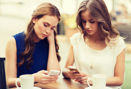young women: technology, internet addiction, lifestyle, friendship and people concept - young women or teenage girls with smartphones and coffee cups at cafe outdoors
