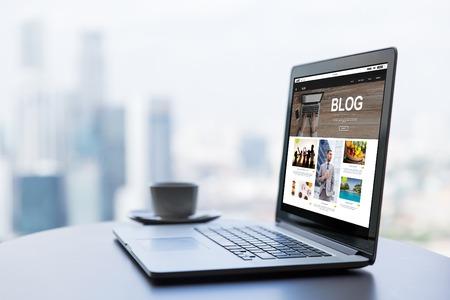 Technologie, podnikání, masmédia, internet a moderní životní koncept - zavřít otevřený přenosný počítač s blog webovou stránku na obrazovce a šálek kávy na stůl v kanceláři nebo hotelové místnosti