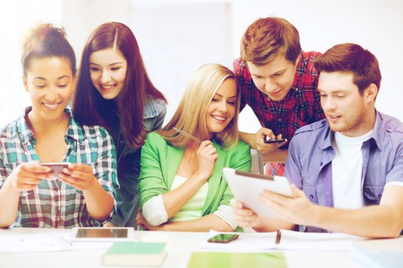 internet education: education, technology and internet - students looking at smartphones and tablet pc Stock Photo