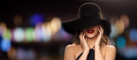 celebrities: people, luxury and fashion concept - beautiful woman in black hat over blurred night lights background