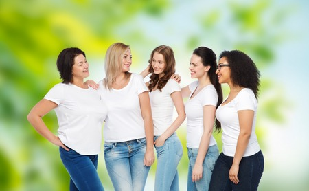 natural backgrounds: friendship, diverse, body positive and people concept - group of happy different size women in white t-shirts hugging over green natural background Stock Photo