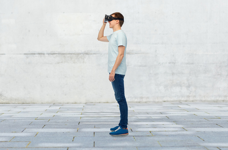 entertainment background: 3d technology, virtual reality, entertainment, cyberspace and people concept - happy young man with virtual reality headset or 3d glasses over street background