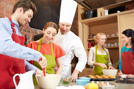 cooking class, culinary, bakery, food and people concept - happy group of friends and male chef cook baking in kitchen photo