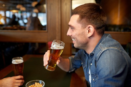 alcohol drinks: people, drinks, alcohol and leisure concept - happy young man drinking draft beer at bar or pub