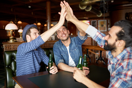 bottled beer: people, leisure, friendship, gesture and bachelor party concept - happy male friends drinking bottled beer and making high five at bar or pub Stock Photo