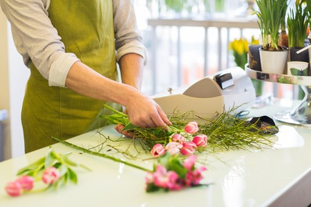 people, business, sale and floristry concept - close up of florist man making bunch at flower shop Zdjęcie Seryjne - 63415736