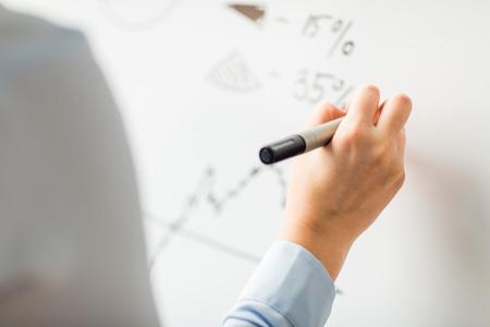 비즈니스, 사람, 경제, 분석 및 통계 개념 - 가까운 사무실 화이트 보드에 마커 쓰기와 손 최대