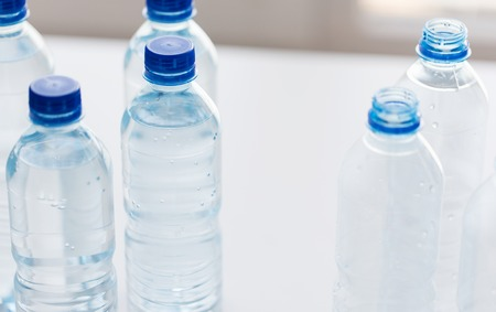 water concept: recycling, healthy eating and food storage concept - close up of plastic bottles with pure drinking water on table