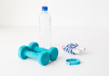 sport, healthy lifestyle and objects concept - close up of dumbbells, fitness tracker, skipping rope and water bottle with water over white background