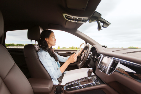 driving a car: leisure, road trip, technology, travel and people concept - happy woman driving car with smarhphone