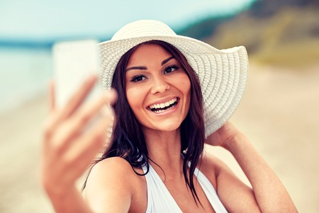 cell phone: lifestyle, leisure, summer, technology and people concept - smiling young woman or teenage girl in sun hat taking selfie with smartphone on beach Stock Photo