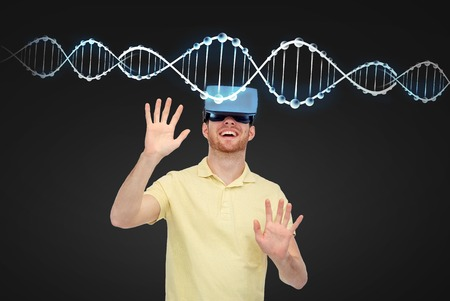 entertainment background: 3d technology, virtual reality, entertainment and people concept - happy young man with virtual reality headset or 3d glasses playing game over black background and dns molecule