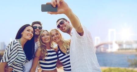 De zomer vakantie, reizen, toerisme, technologie en mensen concept - groep lachende vrienden met smartphone fotograferen en het nemen van selfie over regenboog brug in Tokio in Japan achtergrond Stockfoto - 63606491