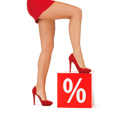 mini dress: people, sale, discount and shopping concept - close up of woman legs in red shoes with percent sign