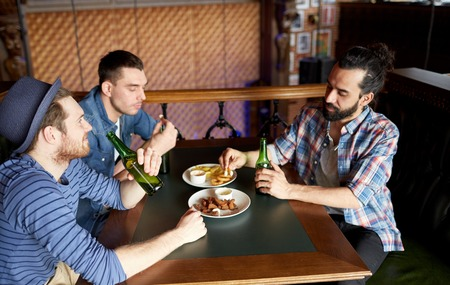 middle eastern clothing: people, leisure, friendship and bachelor party concept - happy male friends drinking bottled beer and eating snacks at bar or pub
