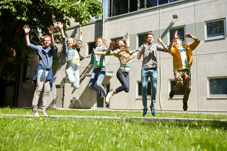 posing  agree: friendship, motion, action, freedom and people concept - group of happy teenage students or friends jumping outdoors