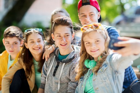 school teens: education, high school, technology and people concept - group of happy teenage students or friends taking selfie by smartphone