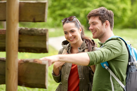 showing: adventure, travel, tourism, hike and people concept - smiling couple with backpacks looking at signpost outdoors
