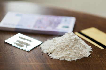 narcotic: drug use, crime, addiction and substance abuse concept - close up of crack cocaine drug dose track on mirror with credit card and money