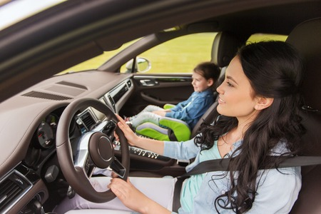 driving a car: family, transport, road trip and people concept - happy woman with little daughter driving in car Stock Photo