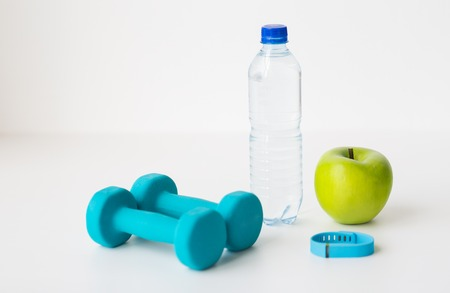 sport, healthy lifestyle and objects concept - close up of dumbbells with fitness tracker, green apple and water bottle over white background Stock Photo