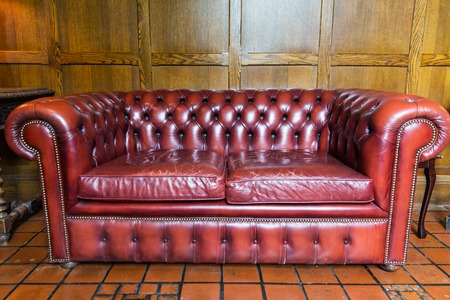 coziness: comfort, antique furniture and interior concept - close up of vintage leather sofa