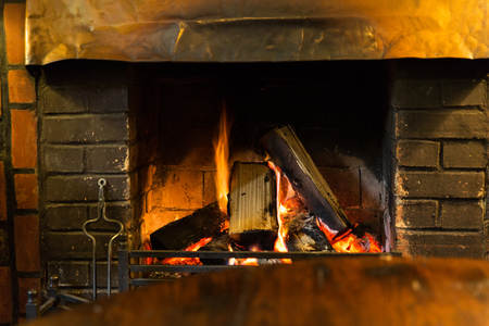 hotbed: stove heating and fire concept - close up of burning fireplace at home