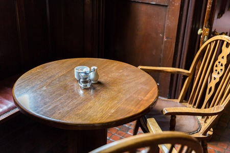 vintage objects: interior and objects concept - close up of vintage pub table and chairs in irish pub or cafe