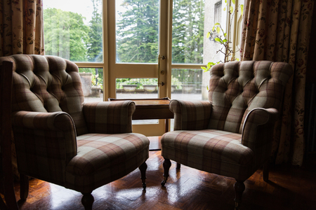 coziness: interior, furniture and objects concept - close up of vintage armchairs and table at hotel room or home Stock Photo