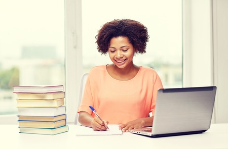 essay: people, technology and education concept - happy african american young woman sitting at table with laptop computer and books at home