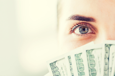 american banker: business, finance, saving, banking and people concept - close up of woman hiding her face behind us dollar money fan Stock Photo