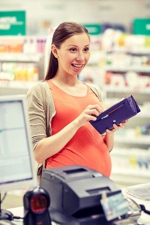 pharmaceutics: medicine, pharmaceutics, health care and people concept - happy pregnant woman with wallet in at cashbox drugstore