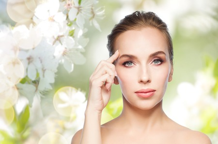 forehead: beauty, people and plastic surgery concept - beautiful young woman showing her forehead over natural spring cherry blossom background