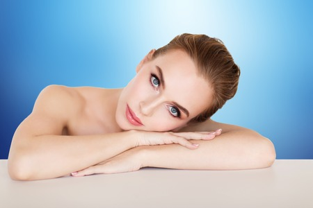 beauty, people and bodycare concept -beautiful young woman face and hands over blue background