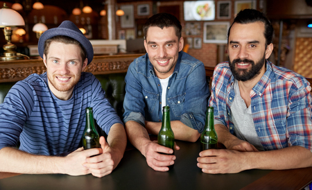 bottled beer: people, leisure, friendship and bachelor party concept - happy male friends drinking bottled beer at bar or pub